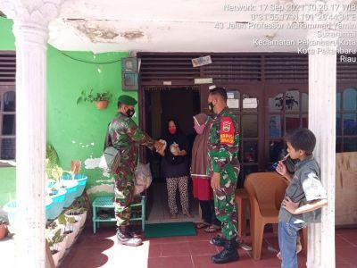 Duo Babinsa Simpang Empat Door to Door Bagikan Nasi Bungkus ke Warga